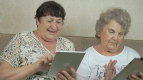 Two elderly sisters holding silver digital tablets. Two elderly sisters sitting on a beige sofa at home. Each woman holds the silver digital tablet stock video
