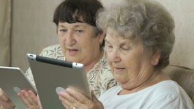 Two elderly sisters holding silver digital tablets. Two elderly sisters sitting on a beige sofa at home. Each woman holds the silver digital tablet stock footage