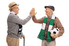 Two elderly soccer fans high-fiving each other Royalty Free Stock Photos