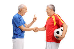 Two elderly soccer players shaking hands Royalty Free Stock Image
