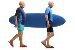 Two elderly surfers walking and carrying a surfboard. Full length profile shot of two elderly surfers walking and carrying a surfboard isolated on white Stock Photography