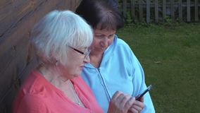 Two elderly woman browsing mobile phone together in countryside garden. Senior woman using smart phone in summer garden stock video