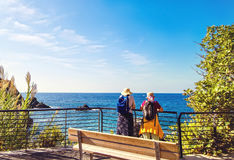 Two elderly women backpacking near sea. Two elderly women in hats with backpacks looking at the sea stock photography