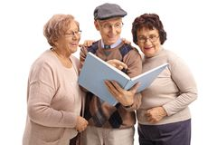 Two elderly women and an elderly man reading a book together. Two elderly women and an elderly men reading a book together isolated on white background Stock Photo