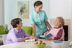 Two elderly women and a friendly nurse. Two elderly women reading and talking to a smiling nurse stock photos