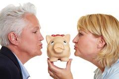 Two elderly women kissing piggy. Side view of two senior women kissing a piggy bank Royalty Free Stock Photo