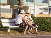 Two elderly women sitting on a bench and talk on the promenade Royalty Free Stock Photo