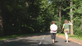 Two elderly women are walking in the woods on a summer day.  stock video footage