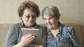 Two elderly women watch pictures using a tablet stock video footage
