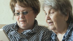 Two elderly women watch pictures using a tablet. Two elderly women sit on the couch and watch pictures using a digital tablet stock video footage