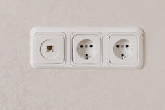 Two electric outlets on wall EU standart and telephone plug. Stock Image