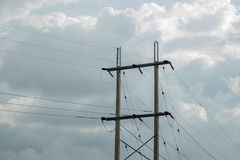 Electric poles beside main road in cloudy stock images