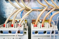 Two electric three-phase switches connected by wires on a metal background. royalty free stock photos