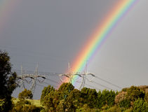 Two electrical pylons with rainbow Stock Photography