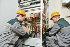 Two electrician workers. Two electrician builder engineer works with electric cable wiring of fuse switch box Royalty Free Stock Image