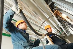 Two electrician workers at cabling. Two electrician builder engineers workers installing industrial cable into fuse box Royalty Free Stock Photos