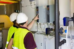 Two electricians checking the power panel. In a power plant stock photography