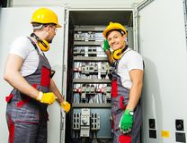Two electricians on a factory. Two electricians in a safety hat and headphones on a factory royalty free stock image