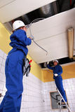 Two electricians. Repairing ceiling lighting Stock Image