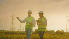 Two electricians work together, standing in the field near electricity transmission line in helmets. Standing in the. Two electricians work together, standing in stock video footage