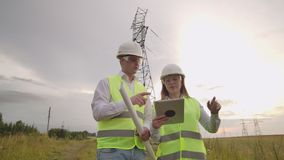 Two electricians work together, standing in the field near electricity transmission line in helmets. Standing in the. Two electricians work together, standing in stock footage