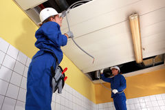 Two electricians. Working on ceiling wiring Royalty Free Stock Photos