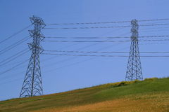 Two Electricity Pylons. On a hill over clear blue sky Stock Photography