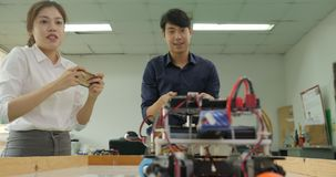 Two electronics engineer programming and control robots to playing soccer. Two electronics engineer programming and control robots to playing soccer with mobile stock video