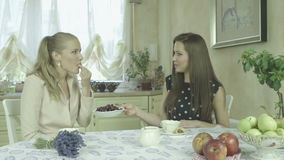 Two elegant attractive smiling young women having coffee time at dining table stock footage