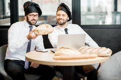Bakers working with bread in the office. Two elegant bakers in white shirts and caps checking the quality of the bread loaves sitting in the bakery office stock photo