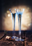 Two elegant blue tinted flutes of champagne. Two elegant blue tinted flutes of luxury champagne with a champagne bottle cork on a rustic wooden bar counter with stock photography