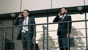 Two elegant businessmen doing business on the mobile phones standing near the office building stock video