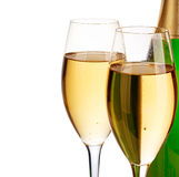 Two elegant champagne glasses on the background of green bottles close-up isolated on  a  white. Festive still life. Stock Image