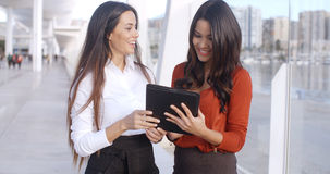 Two Elegant Dressed Business Women Talking. Two Happy  Smiling  Elegant Dressed Business Women Talking With Each Other About Their Project on Tablet Device Royalty Free Stock Photos