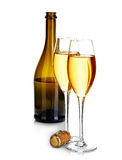 Two elegant glasses of champagne on the background of brown bottles close-up isolated on a white. Festive still life. Royalty Free Stock Images