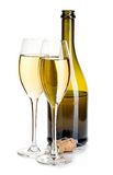 Two elegant glasses of champagne on the background of brown bottles close-up  on a white. Festive still life. Stock Photography