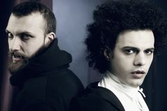 Two elegant handsome vampires looking camera stock images