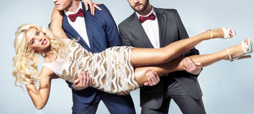 Two elegant men caryying a stunning woman Stock Photo