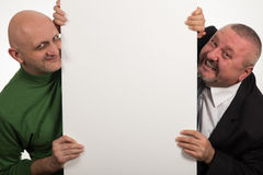 Two elegant men smiling after an empty panel on white background Royalty Free Stock Images