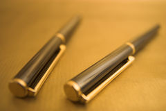 Two elegant pens. Two Pens on Gold Background Royalty Free Stock Image