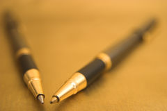 Two elegant Pens. Two Pens on Gold Background Stock Images