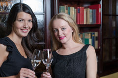 Two elegant sophisticated women. Two elegant sophisticated young women in stylish black evening wear celebrating together drinking flutes of champagne in a hotel stock photography