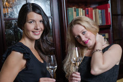 Two elegant sophisticated women. Two elegant sophisticated young women in stylish black evening wear celebrating together drinking flutes of champagne in a hotel Royalty Free Stock Photo
