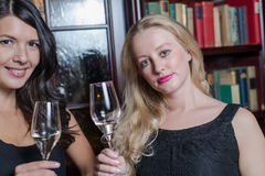Two elegant sophisticated women. Two elegant sophisticated young women in stylish black evening wear celebrating together drinking flutes of champagne in a hotel Stock Photos