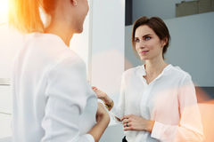 Two elegant women entrepreneurs talking about something while standing in modern office interior, Royalty Free Stock Image