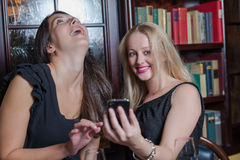 Two elegant women laughing at a text message Stock Photos