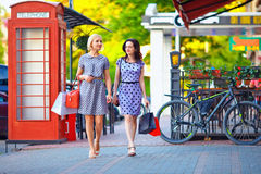 Two elegant women walking the city street Stock Images