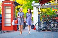 Two elegant women walking the city street stock images