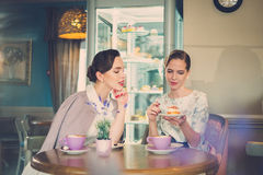 Two elegant young ladies in a cafe.  royalty free stock photography