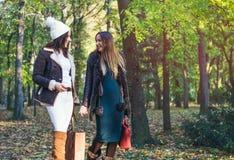 Two elegant young woman walking through a park Royalty Free Stock Photo